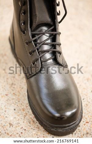 Black Leather Boot on terrazzo floor  - stock photo