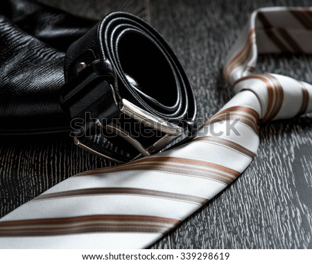 black leather boot strap and tie on a natural background - stock photo