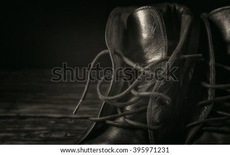 Black leather boots closeup on a black background closeup with copy space. Black and white toning - stock photo