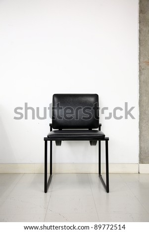 black leather chair over wall - stock photo
