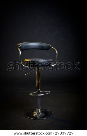 Black leather hair dresser or barber shop stool. Stage lighting with black background. - stock photo