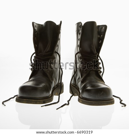 Black leather high top boots with untied laces. - stock photo