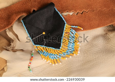 Black leather Native American beaded Medicine Bag against background of assorted animal skins.