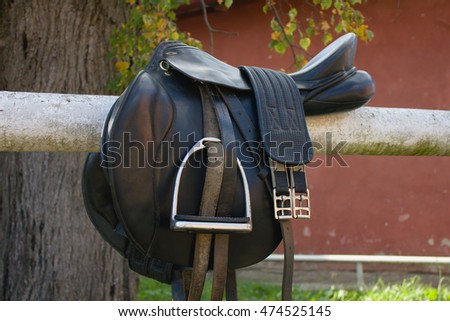 Black leather on a barrier in the stable