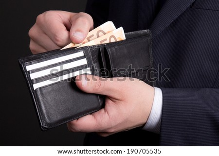 black leather purse with euro banknotes in business man hands - stock photo