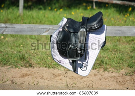 Black leather saddle on the fence - stock photo