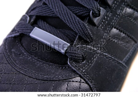 Black leather shoe with tag close up or macro. - stock photo