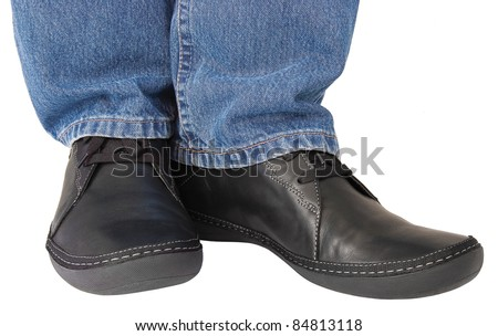Black leather shoes, blue denim indigo jeans, casual men's sneakers closeup, man's feet foot, legs isolated - stock photo