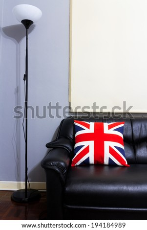 Black Leather Sofa ,union jack backrest Pillow, Floor Lamp on Wood Floor in grey room / interior concept