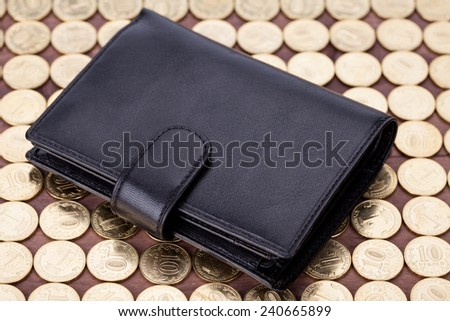 Black leather wallet on golden coins - stock photo