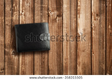 Black leather wallet on wooden table - stock photo