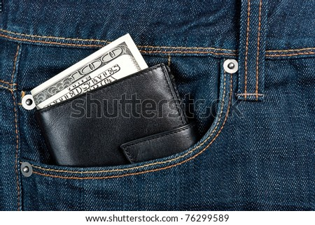 Black leather wallet with dollars in jeans pocket - stock photo