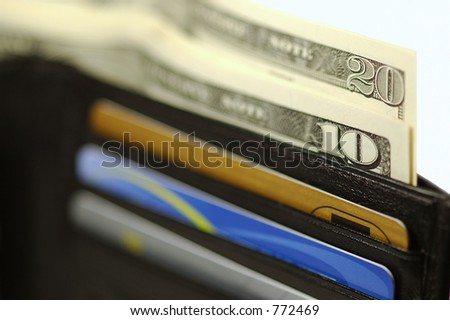 Black leather wallet with money and credit cards. White background.