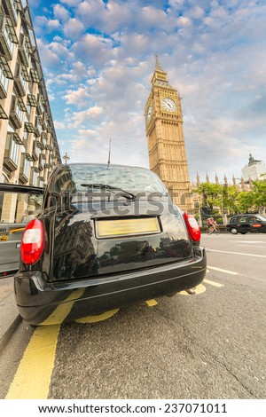 Black London cab under Big Ben tower and Westminster Palace. - stock photo