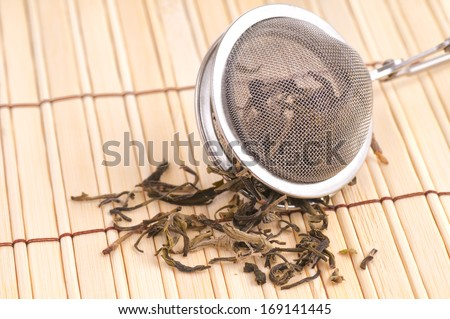 Black Loose Tea Falling out of a Tea Strainer on a Bamboo Mat, drank with water for pleasure and as disease prevention - stock photo