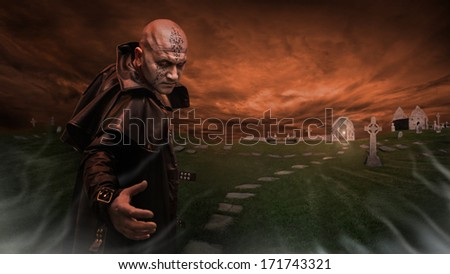 Black Magician in the leather raincoat is inviting you to a graveyard. Focus point on the Magician. - stock photo