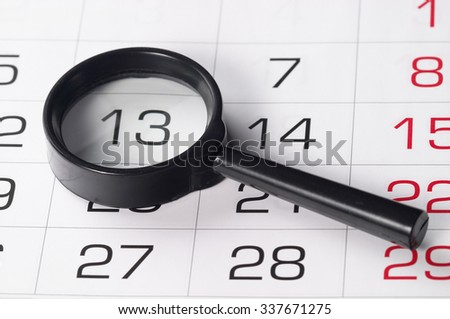 Black magnifying glass over slightly defocused calendar background