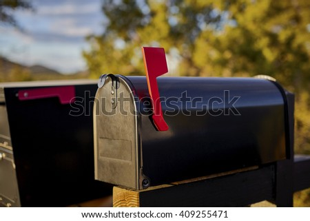 Black Mailbox with red flag up and shallow depth of field - stock photo