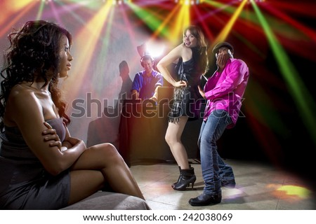 black male cheating on girlfriend with seductive white female at club - stock photo