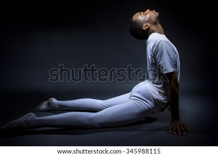 Black male dancer practicing warm up exercises for flexibility.  He is lit for contrast to outline the human body.