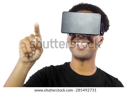 Black male wearing a virtual reality headset on a white background.  He is pointing with his finger like he is interacting with something. - stock photo