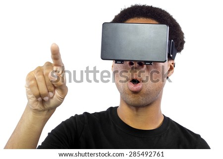 Black male wearing a virtual reality headset on a white background.  He is pointing with his finger like he is interacting with something.