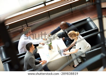 Black man and white man shaking hands during work meeting in modern office. - stock photo