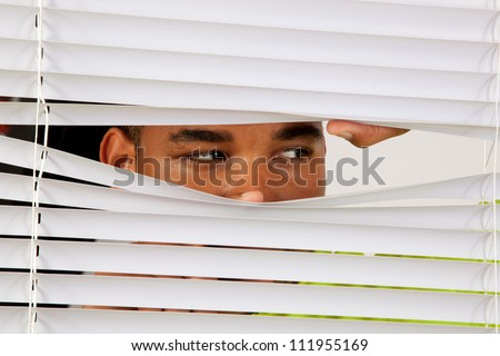 Black man behind window blinds and peering out like he was watching someone or spying