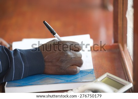 Black man hand with pen filling form on table - stock photo