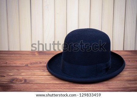 Black man hat on table near wood wall vintage photo - stock photo