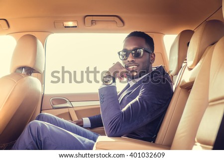 Black man in a suit and sunglasses sitting in a car. - stock photo