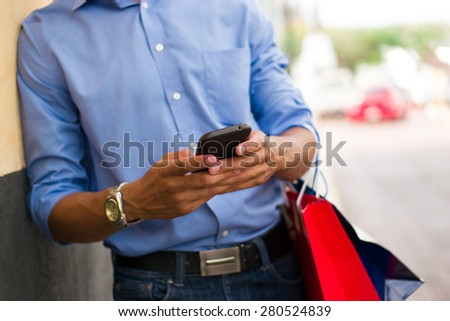 Black man in Casco Antiguo - Panama City with shopping bags. The guy leans on a wall and types message with his phone on social network. Cropped view. - stock photo