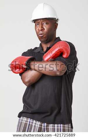 Black man in polo and short, wearing a white hard hat and red boxing glove - stock photo