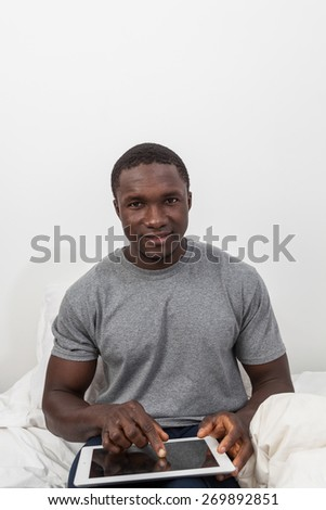 Black man looking at camera and touching his tablet