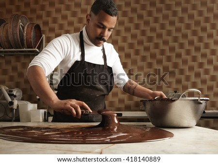 Black man professional chief collects tasty melted chocolate from vintage marble table to big steel pot in his artisan rustic kitchen with industrial retro machines. Mirrored in chocolate on table.