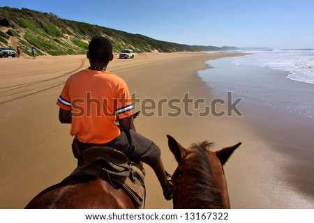 Black man rides a horse on beach. Shot in Sodwana Bay Nature Reserve, KwaZulu-Natal province, Southern Mozambique area, South Africa. - stock photo