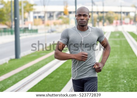 Black man running and listening to music in urban background. Handsome male doing workout outdoors.
