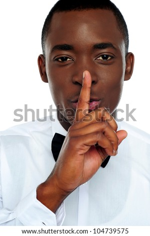 Black man showing silence gesture with finger on his lips. All on white background - stock photo