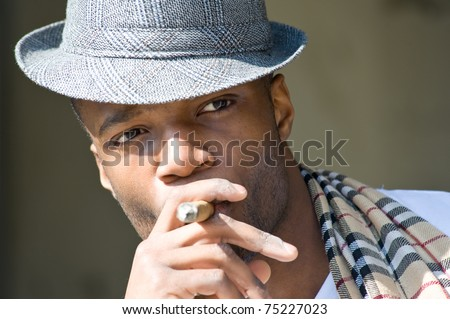 Black man smoking cigar portrait with hat. - stock photo