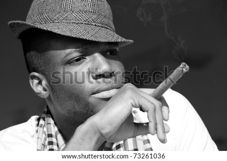 Black man smoking cigar portrait with hat. Black and white photo. - stock photo