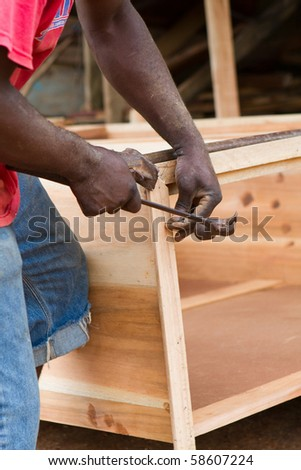 Black man uses hammer and nail to build a dresser chest out of cedar in Jamaica.