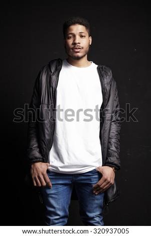 Black Man wearing white t-shirt on black background - stock photo