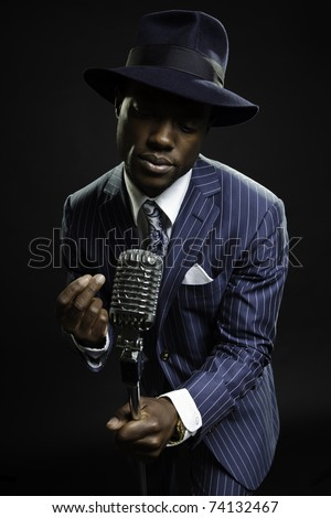 Black man with blue striped suit and blue hat singing. Jazz musician. Night club. Cotton club. New Orleans. - stock photo