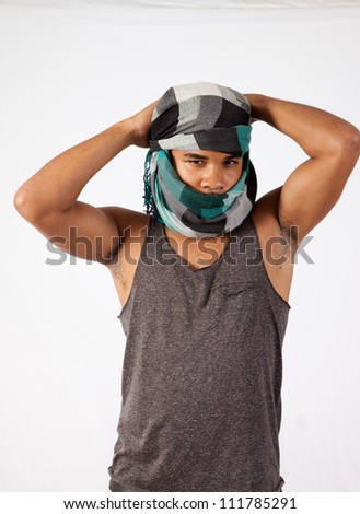 Black man with his head in a turban like an Arab or Mid Eastern man, looking at the camera through his head covering and arranging the wrap - stock photo
