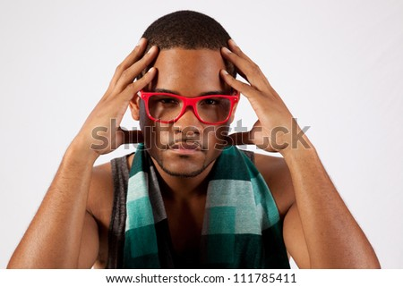 Black man with pink eye glasses whit his hands up to his head, eye contact with the camera and a serious expression