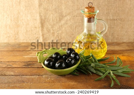 Black marinated olives in green saucepan with oil near branch and oilcan on rustic wooden background - stock photo