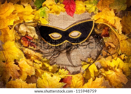 Black masquerade mask and yellow leaves on brown textured background - stock photo