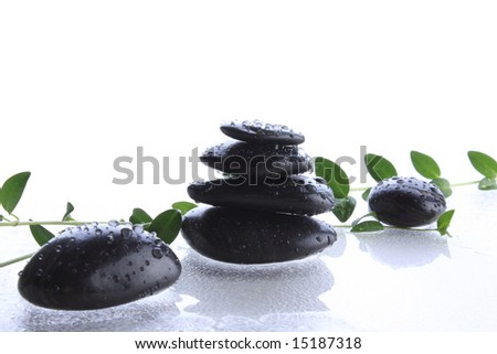 Black massage spa stones on wet surface - stock photo