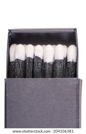 Black matches in a box on a white background macro - stock photo