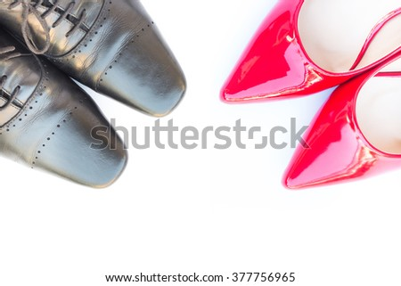 Black men's shoes and red high heel women's shoes on white background - stock photo